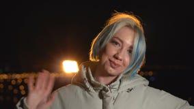 Ritratto di una giovane donna alla notte nella città La ragazza felice attraente ondeggia la sua mano alla macchina fotografica stock footage