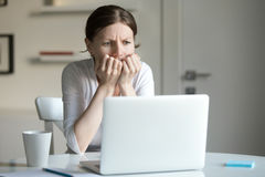 Ritratto di una giovane donna allo scrittorio con il computer portatile, timore immagine stock libera da diritti