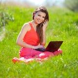Ritratto di una giovane donna astuta che si trova sull'erba e che per mezzo del computer portatile Immagini Stock Libere da Diritti