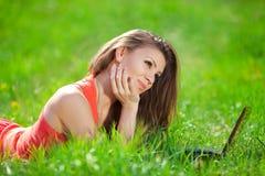 Ritratto di una giovane donna astuta che si trova sull'erba e che per mezzo del computer portatile Fotografie Stock Libere da Diritti