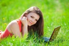 Ritratto di una giovane donna astuta che si trova sull'erba e che per mezzo del computer portatile Immagine Stock