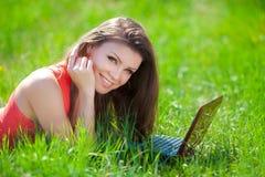 Ritratto di una giovane donna astuta che si trova sull'erba e che per mezzo del computer portatile Immagini Stock