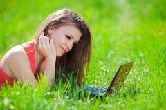 Ritratto di una giovane donna astuta che si trova sull'erba e che per mezzo del computer portatile Fotografia Stock