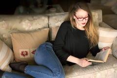 Ritratto di una giovane donna bionda che legge un monocolo d'uso del libro Immagine Stock