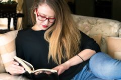 Ritratto di una giovane donna bionda che legge un monocolo d'uso del libro Fotografie Stock Libere da Diritti