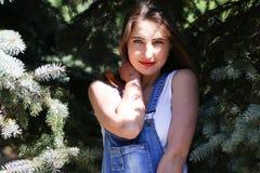 Ritratto di una giovane donna che posa sull'abete rosso del fondo Fotografia Stock