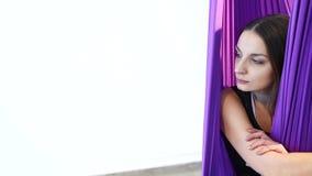 Ritratto di una giovane donna che si siede in un'amaca nello studio Yoga dell'aria archivi video