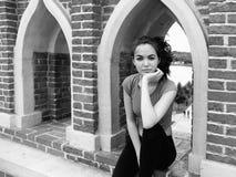Ritratto di una giovane donna che sogna di un muro di mattoni Fotografia Stock