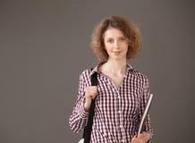 Ritratto di una giovane donna che tiene un libro e una borsa Fotografia Stock