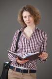 Ritratto di una giovane donna che tiene un libro e una cartella Fotografie Stock