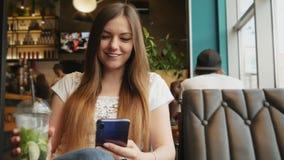 Ritratto di una giovane donna che usa il cellulare al bar, beve cocktail di zanzare fredde archivi video