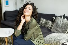 Ritratto di una giovane donna con capelli ricci che si rilassano su un sofà fotografie stock