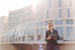 Ritratto di una giovane donna con i vetri, un cappello tricottato e un bomber nero con una compressa elettronica Foto della via immagine stock libera da diritti