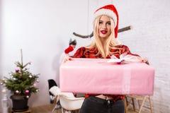 Ritratto di una giovane donna con un giftbox rosa a casa sulla priorità alta Bella bionda in un cappello di Santa, camicia rossa  Fotografia Stock Libera da Diritti