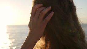 Ritratto di una giovane donna contro il mare con capelli che ondeggiano nel vento, esaminante la sua spalla Donna seducente video d archivio