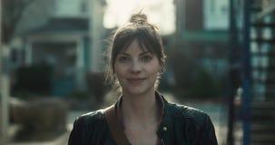 Ritratto di una giovane donna graziosa che sorride alla macchina fotografica archivi video