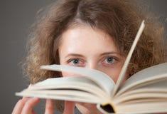 Ritratto di una giovane donna graziosa con libri, fondo grigio Fotografie Stock Libere da Diritti