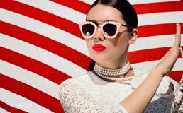 Ritratto di una giovane donna graziosa in dess bianchi del pizzo, collana bianca della perla ed occhiali da sole con le labbra di fotografia stock libera da diritti