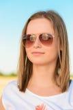 Ritratto di una giovane donna in occhiali da sole Fotografie Stock Libere da Diritti