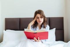 Ritratto di una giovane donna premurosa in libro di lettura dei pigiami Fotografia Stock