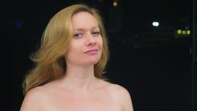 Ritratto di una giovane donna senza trucco con le spalle nude contro le luci confuse della città Copi lo spazio fotografie stock