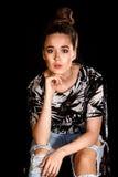 Ritratto di una giovane donna sopra fondo nero Immagine Stock