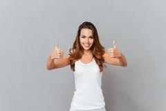 Ritratto di una giovane donna sorridente casuale che mostra i pollici su Fotografia Stock Libera da Diritti