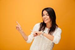 Ritratto di una giovane donna sorridente che indica le dita via fotografia stock
