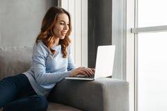 Ritratto di una giovane donna sorridente che per mezzo del computer portatile Immagine Stock