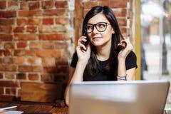 Ritratto di una giovane donna sorridente che per mezzo del computer portatile e parlando sul telefono cellulare Fotografia Stock
