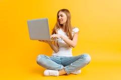 Ritratto di una giovane donna sorridente, sedentesi a gambe accavallate facendo uso di un computer portatile, su un fondo giallo fotografia stock
