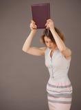 Ritratto di una giovane donna stancata con un libro Fotografia Stock Libera da Diritti