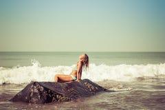Ritratto di una giovane donna sui precedenti delle onde e delle pietre immagine stock