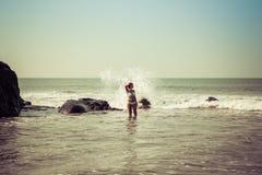 Ritratto di una giovane donna sui precedenti delle onde e delle pietre fotografie stock