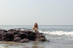 Ritratto di una giovane donna sui precedenti delle onde e delle pietre fotografia stock libera da diritti