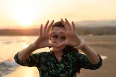 Ritratto di una giovane donna sulla spiaggia al tramonto rosso, cuore delle dita, messaggio di amore fotografia stock