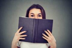Ritratto di una giovane donna sveglia che si nasconde dietro un libro aperto e che esamina macchina fotografica fotografia stock