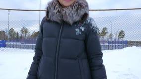 Ritratto di una giovane donna in vestiti caldi su una vecchia pista di pattinaggio di pattinaggio su ghiaccio video d archivio