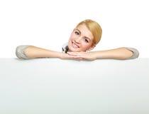Ritratto di una giovane donna vicino alla carta in bianco - più fotografia stock libera da diritti