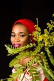 Ritratto di una giovane signora con le foglie verdi nei precedenti immagine stock libera da diritti