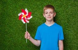 Ritratto di una girandola della tenuta del ragazzo sopra erba Fotografie Stock Libere da Diritti
