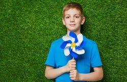 Ritratto di una girandola della tenuta del ragazzo sopra erba Immagini Stock Libere da Diritti