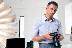 Ritratto di una macchina fotografica bella della tenuta dell'uomo fotografia stock libera da diritti