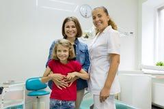 Ritratto di una madre felice con il bambino ed il dentista di medico, in ufficio dentario fotografia stock libera da diritti