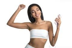 Ritratto di una musica d'ascolto della donna afroamericana sveglia allegra in cuffie e di ballare isolato su bianco Immagine Stock Libera da Diritti