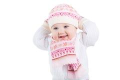 Ritratto di una neonata divertente in un cappello, in una sciarpa ed in un guanto tricottati Immagine Stock Libera da Diritti