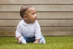 Ritratto di una neonata di sei mesi che si siede sull'erba sulla a immagini stock