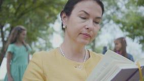 Ritratto di una nonna senior elegante che legge il libro nel parco nella priorit? alta Lle cifre vaghe di due che giocano stock footage