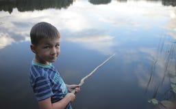 Ritratto di una pesca del ragazzo nel lago che riflette il cielo Fotografia Stock
