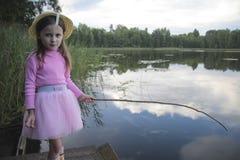Ritratto di una pesca della ragazza nel lago che riflette il cielo Fotografia Stock